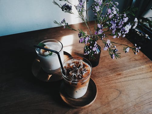 Two Clear Drinking Glasses Beside Flowers on Table