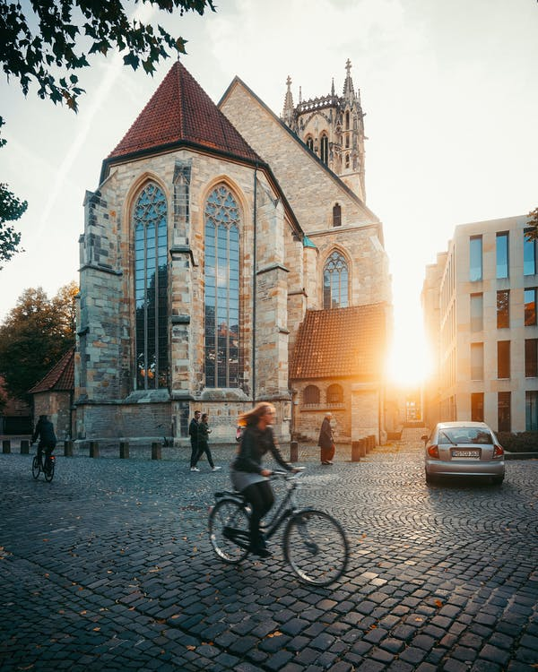 Woman Riding on Bike Outside Buildings