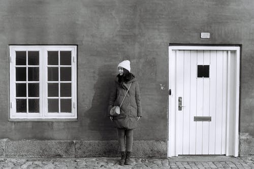 Black and white full body of young female in warm outerwear standing near wall of residential house