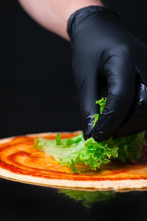 Person With Gloves Putting Lettuce on Pizza