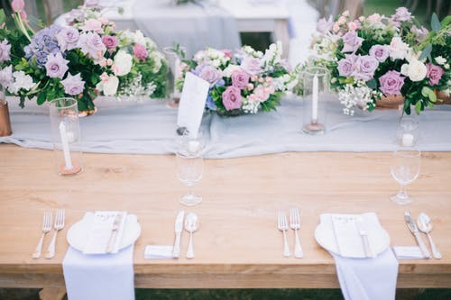 Banquet table with flower bouquets and cutlery on wedding day