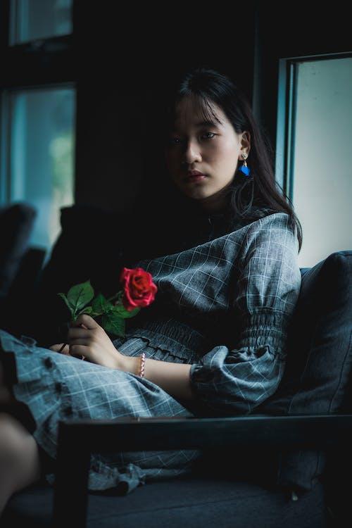Woman Wearing Grey Dress Sitting on Sofa Holding Red Rose