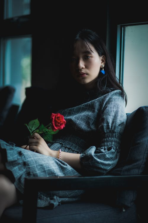 Woman Wearing Grey Dress Sitting on Sofa Holding Red Rose