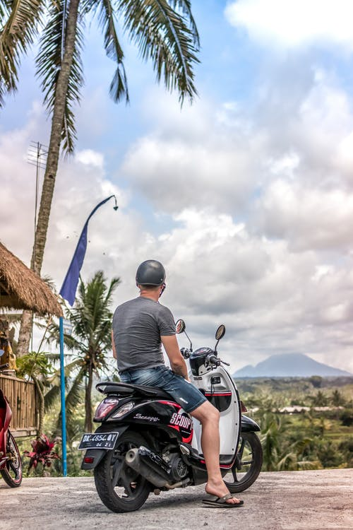 Man Riding A Motor Scooter Parked Near Coconut Tree