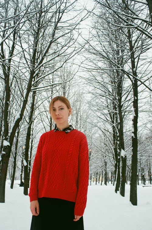 Woman in Red Long-sleeved Top Standing Outdoors