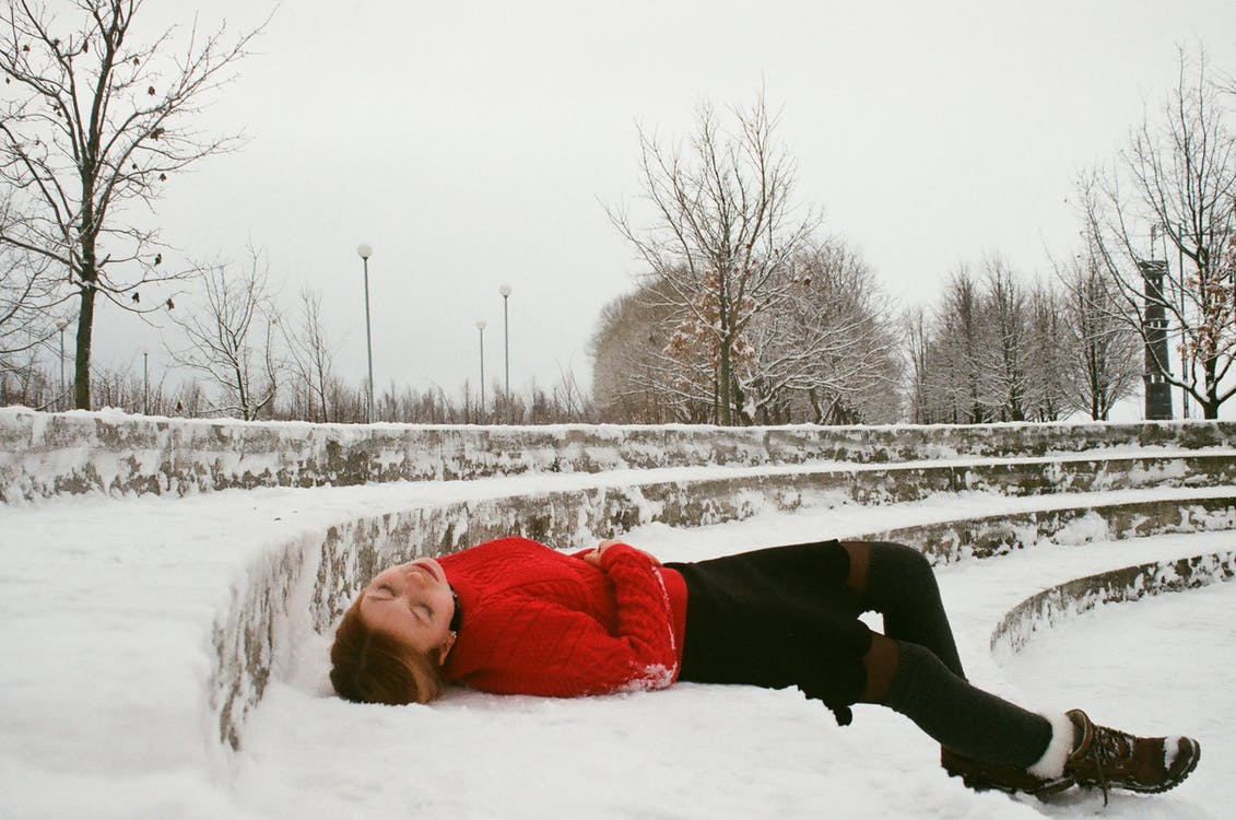 Woman Wearing Red Sweater Lying on Snow Covered Ground