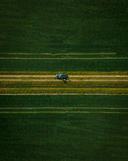 Vehicle On Road In The Middle Of Grass Field