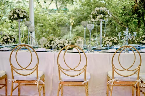 Three Yellow Padded Chairs Beside Table