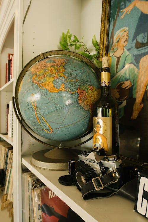 Blue Desk Globe Near Brown Bottle on Shelf