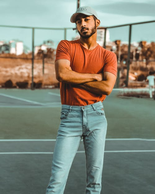 Man Wearing Orange Crew-neck T-shirt and Blue Denim Jeans Standing on a Court