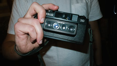 Person Holding Black Nimslo Camera