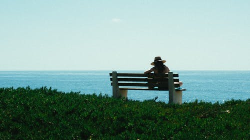 Woman Sitting on Bench on Grass Shore during Day
