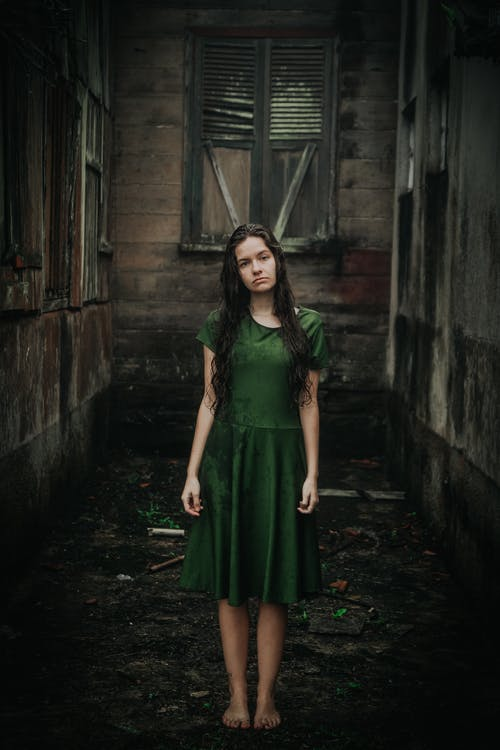 Woman in Green Dress Standing Outdoors