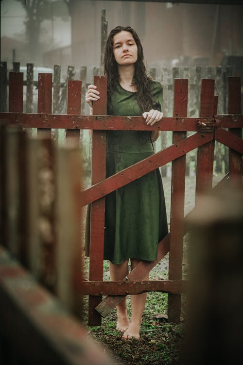 Woman in Green Top Standing By the Fence