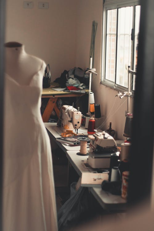 White Dress on Mannequin Beside White Sewing Machine