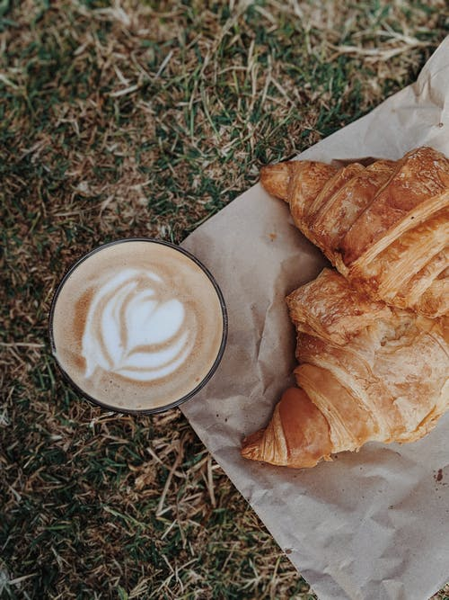 Cappuccino by Croissant on Ground