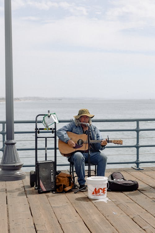 Person Wearing Blue Denim Jacket and Denim Jeans Playing Acoustic Guitar on Boardwalk