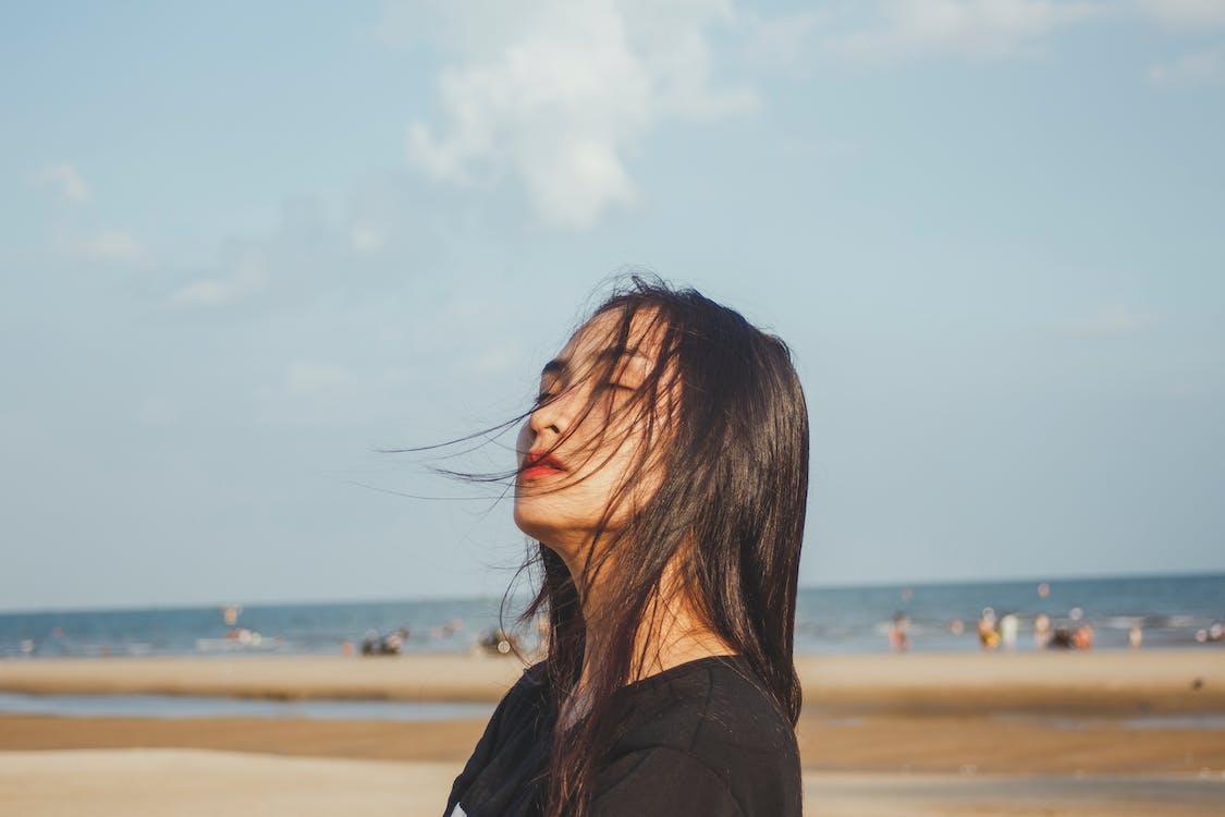 Woman Closing Eyes in Seashore