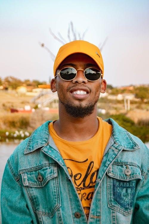 Man in Denim Jacket Yellow Cap and Sunglasses Smiling