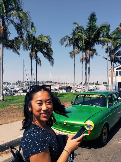 Woman Stands and Smiles Near Green Car