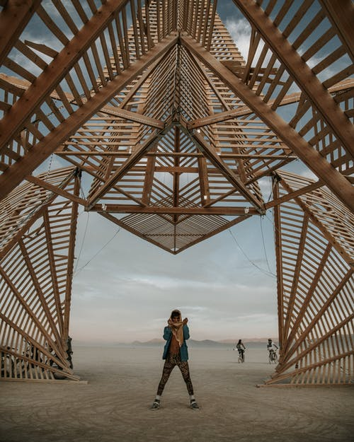 Man Standing Below A Wooden Structure