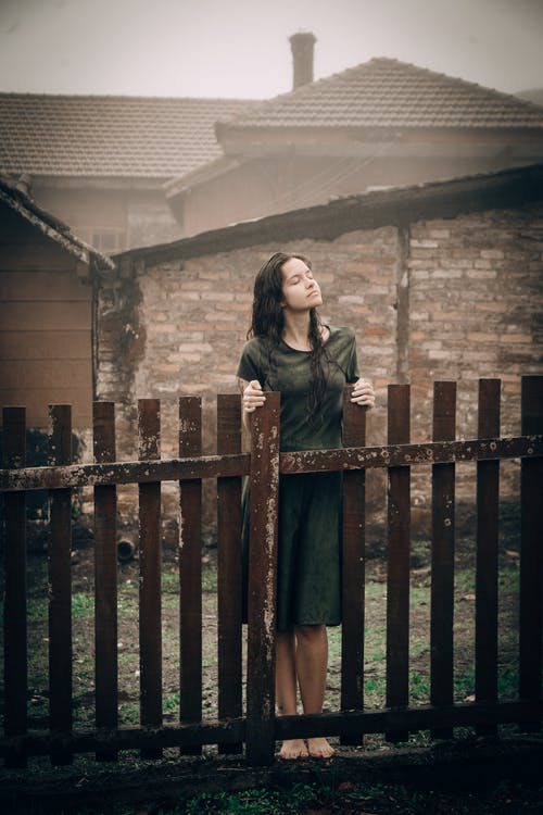 Woman Standing Beside Fence