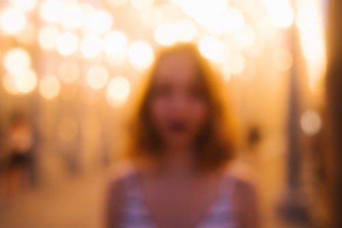 Defocused woman on glowing street