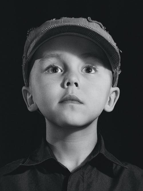 Greyscale Photography of Boy Wearing Hat