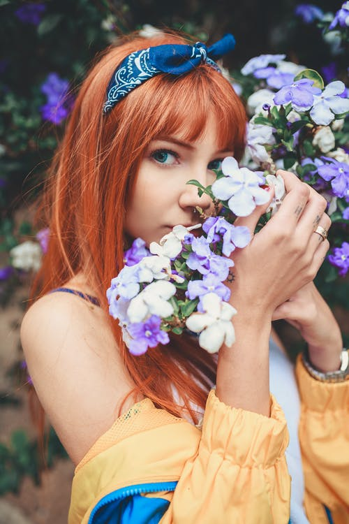 Woman With Bandana Smelling Purple And White Flowers