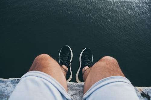 Person in Blue Denim Shorts and Black and White Sneakers Sitting on Boat