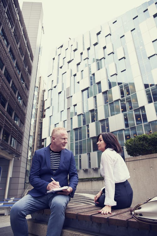 Man and Woman Sitting on Wooden Bench Outside Buildings