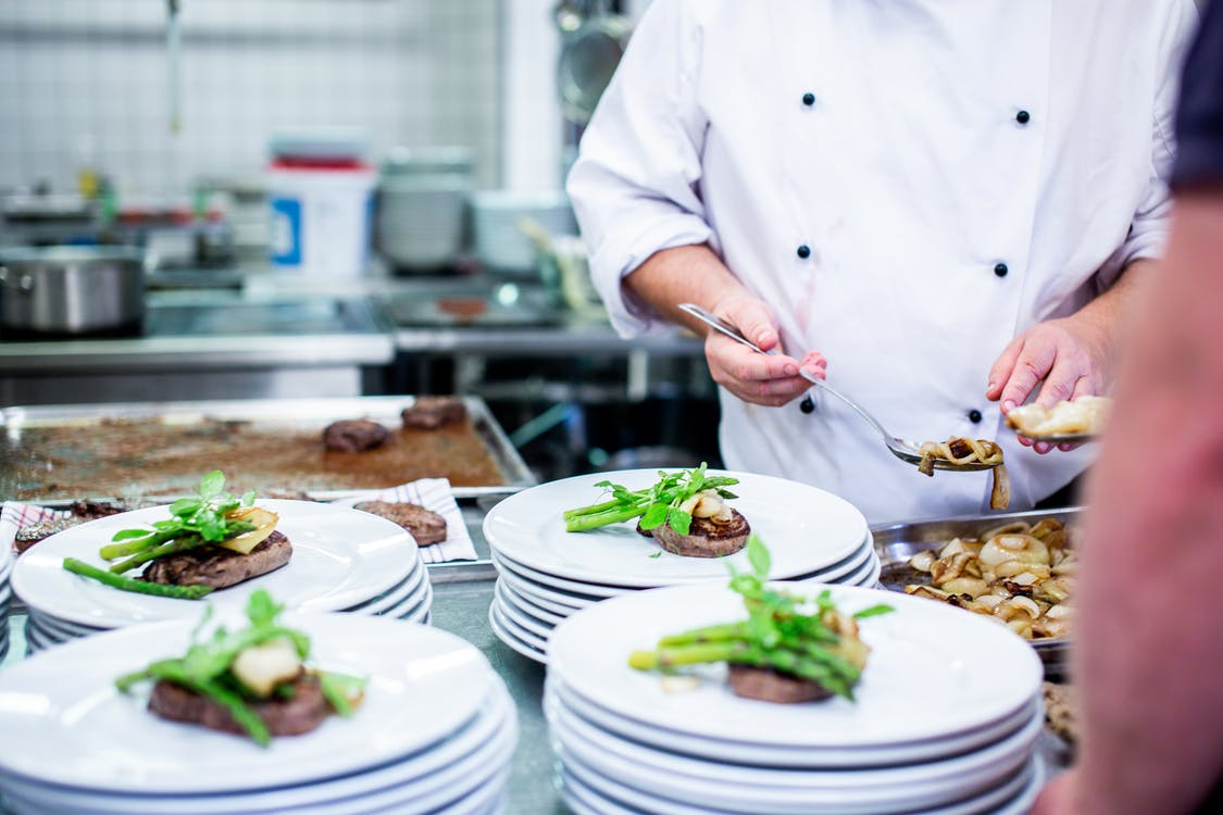 Man in White Top Standing Beside Plates