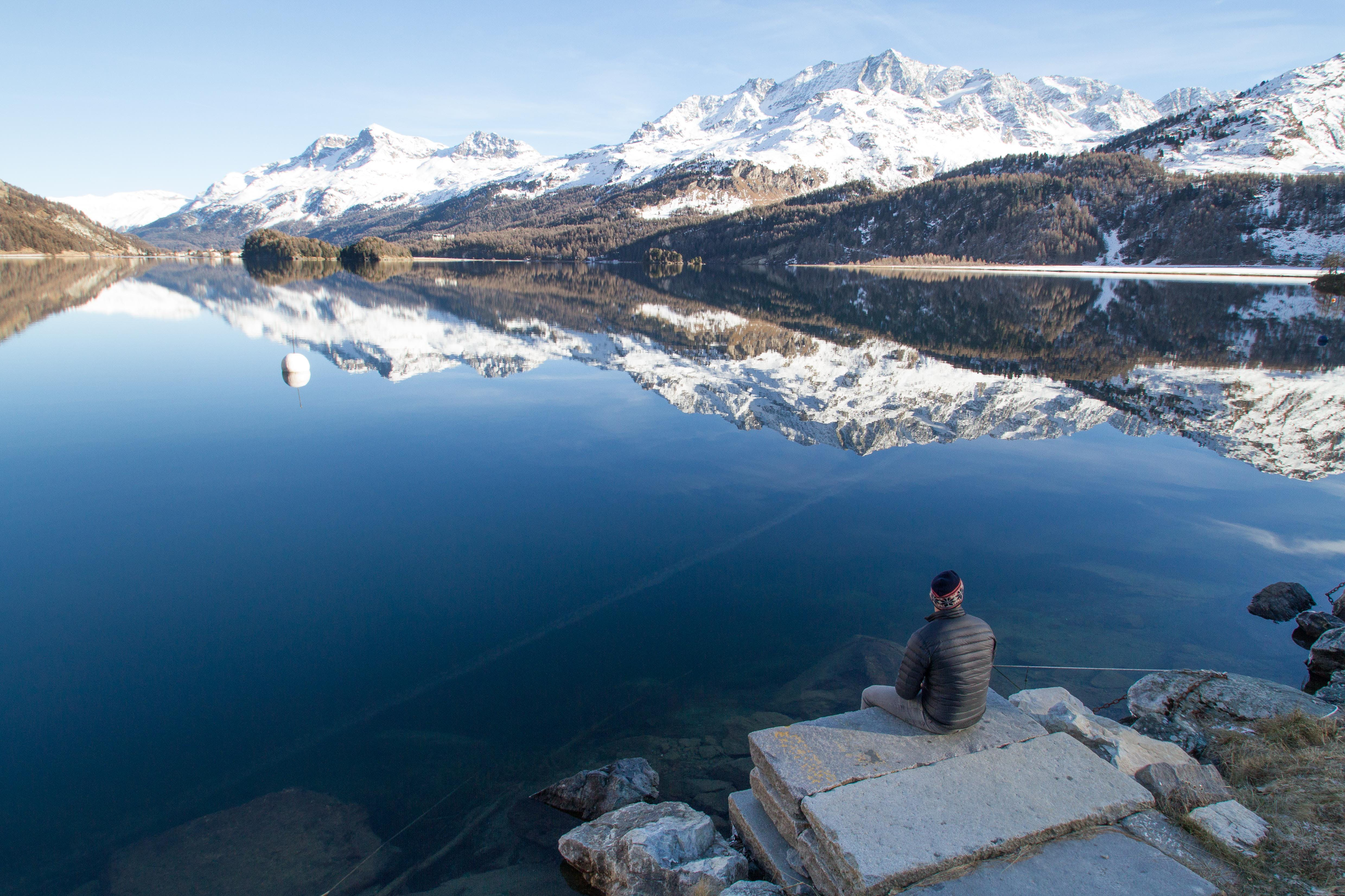 Man Sitting at the Edge of Rock Facing the Lake during Day