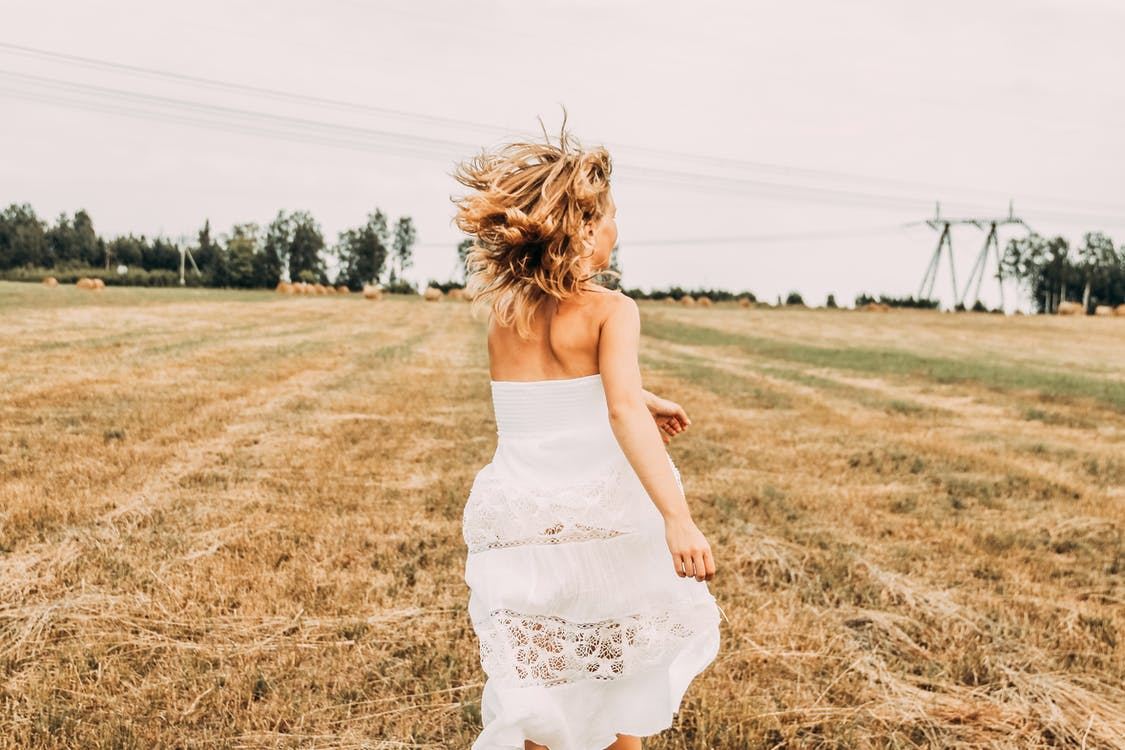 Woman Wearing White Off-shoulder Long Dress While Running on Brown Grass Field