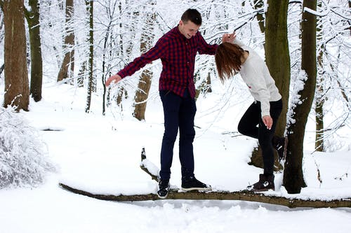 Man and Woman Standing on Wood Branch