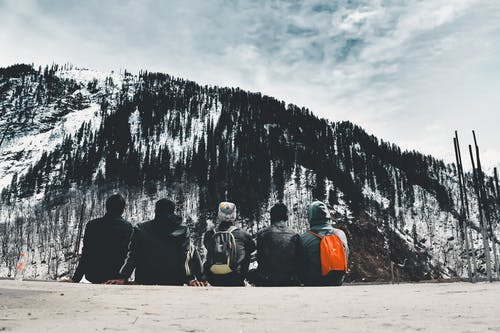 Five People Sitting in Front of Mountain