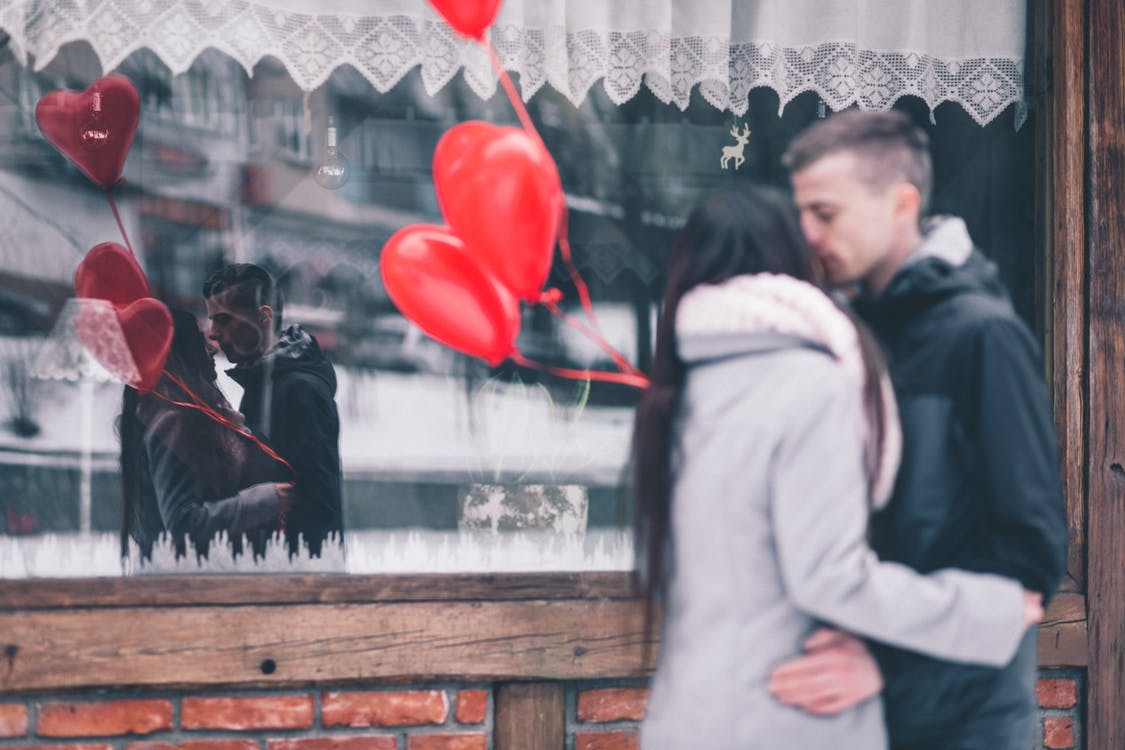 Woman and Man Kissing in Front of Glass Window Store
