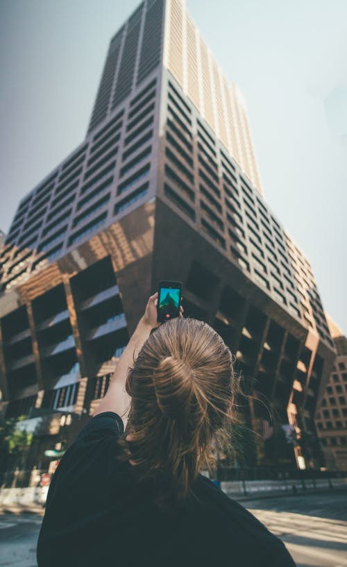 Woman Taking a Picture of a High-rise Building during Day