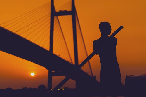 Silhouette Of Man Near A Bridge during Golden Hour