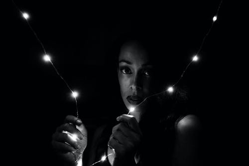 Grayscale Portrait Photo of Woman Holding String Lights