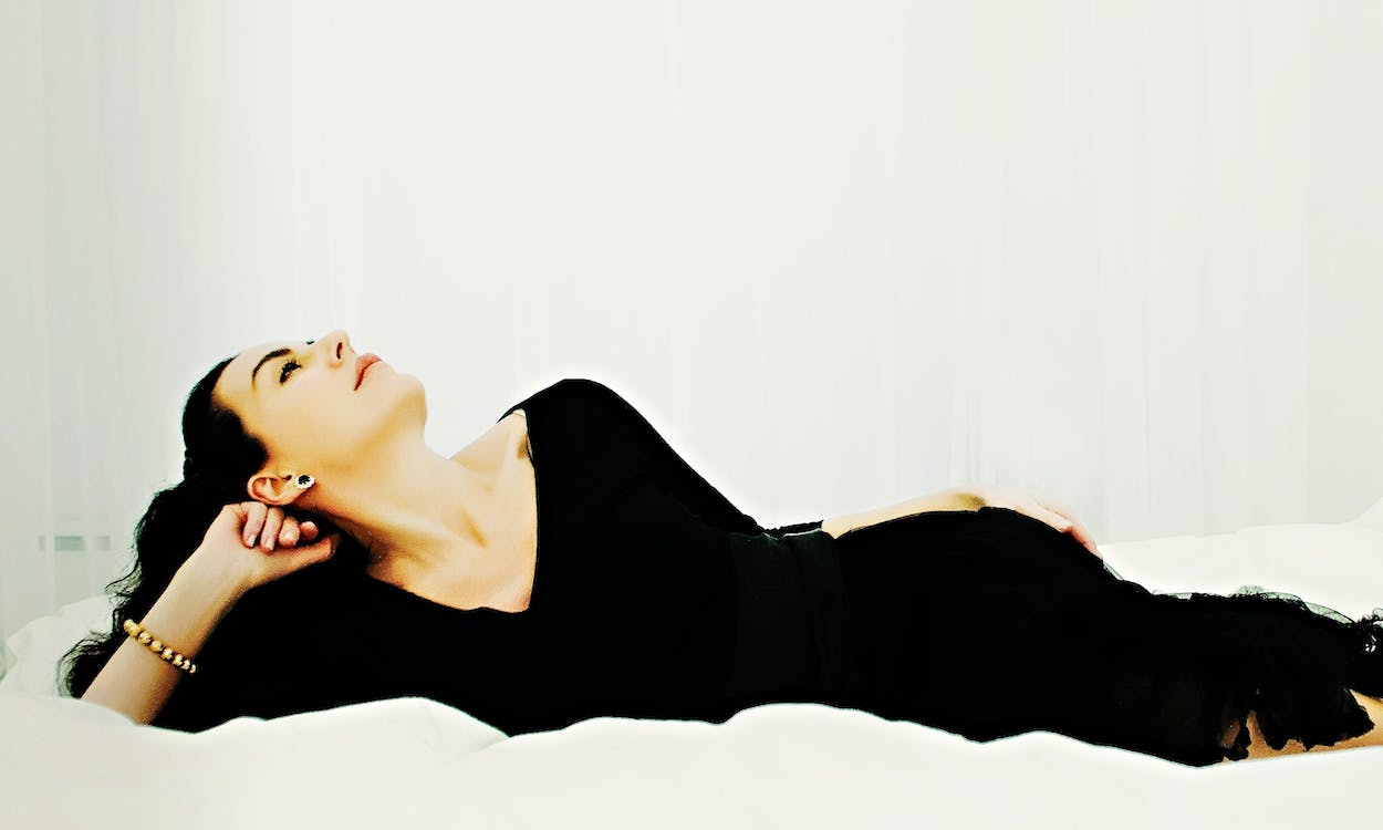Woman in Black Dress Laying on Bed Looking Up