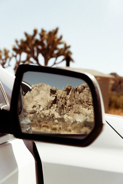 Black and White Wing Mirror Showing Brown Rocky Cliff