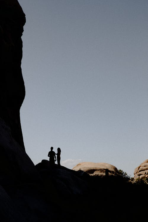 Silhouette of Two People Standing on Rock
