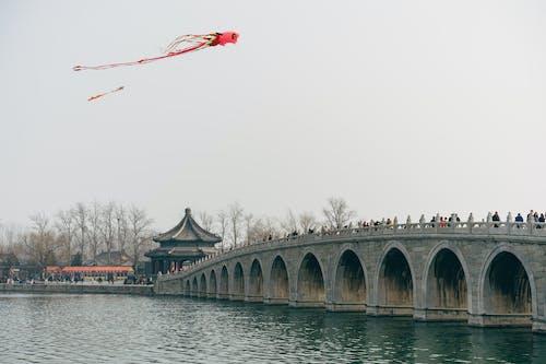 People On A Bridge Watching Kites Fly