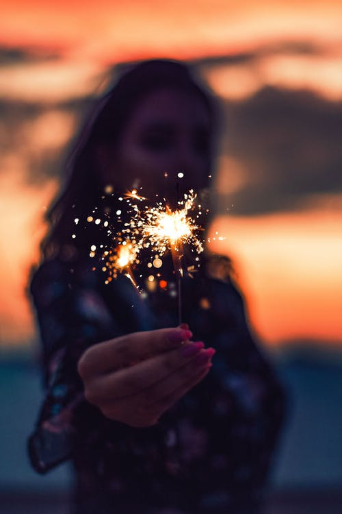 Woman Holding Sparkler during Night Time