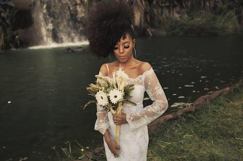 Mulher Em Um Vestido Branco Segurando Flores