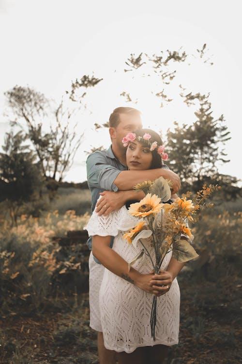Foto De Foco Raso Homem Abraçando Uma Mulher Segurando Flores Amarelas