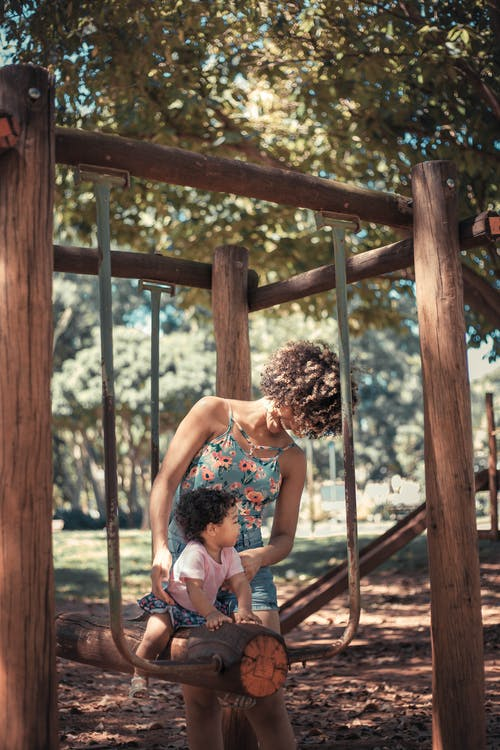Girl Riding on Tree Log Swing Beside Woman Wearing Floral Dress