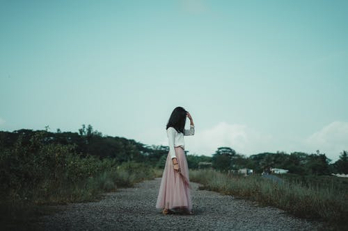 Woman in White and Pink Dress Standing on Gray Dirt Road