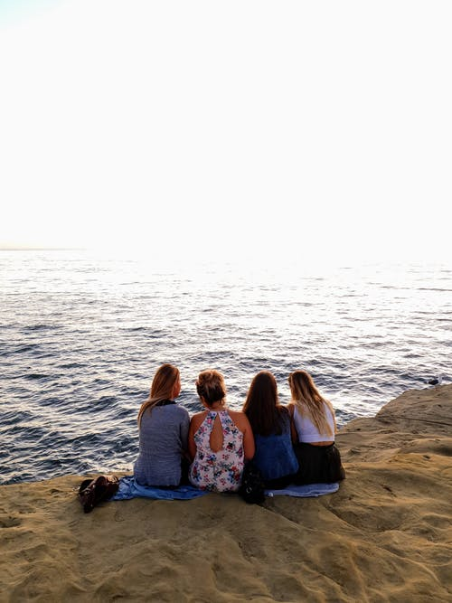 Back view Photo of Four Woman Sitting on the Seashore